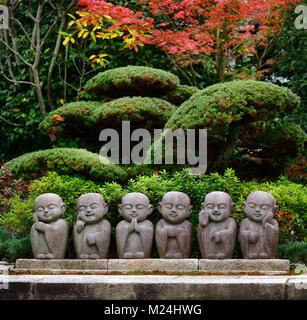 Six cute little monks, Buddhas, stone statues, kawaii garden decor in Kyoto, Japan - Stock Photo