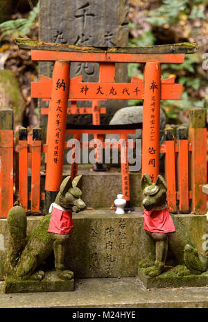 Foxes, Kitsune, at a small private worship Tsuka shrine altar, one of the thousands little Shinto shrines at Fushimi - Stock Photo