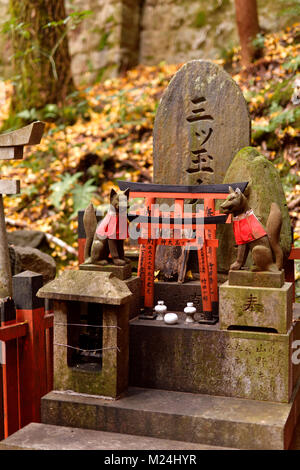 Private worship shrine altar, Tsuka, with Kitsune, messenger foxes. One of the thousands little Shinto shrines at - Stock Photo