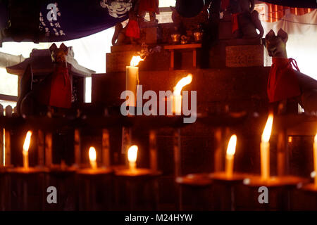 One of the Shinto shrines at Fushimi Inari complex with lit candles and Kitsune foxes. Fushimi Inari-Taisha head - Stock Photo