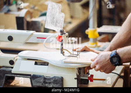 Carpenter engaged in processing wood at the sawmill. - Stock Photo