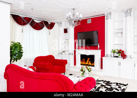 Classical red living room interior space with fire place and red furniture - Stock Photo