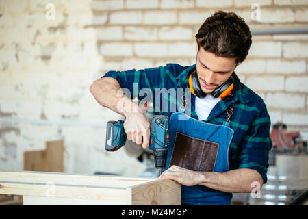 Wood boring drill in hand drilling hole in wooden bar - Stock Photo
