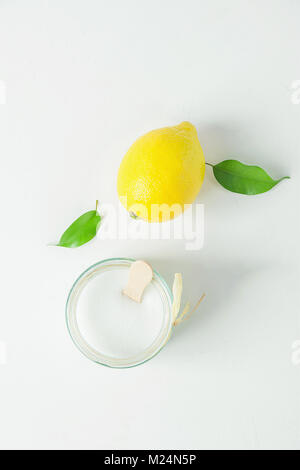 Ripe Yellow Lemon Green Citrus Leaves Sugar in Glass Jar. Ingredients for Face Scrub on White Concrete Stone Tabletop. - Stock Photo