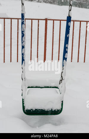 Swing at the playground covered with snow after a heavy snowfall - Stock Photo