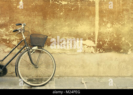 detail of a part of a bicycle leaning against an old wall - Stock Photo