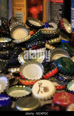 Used beer bottle tops have been collected and are piled up against some beer bottles yet to be emptied. - Stock Photo