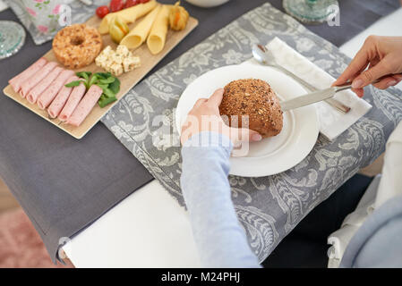 Woman slicing a healthy wholegrain bread roll on a plate at the table with an assortment of cold meats and cheese - Stock Photo
