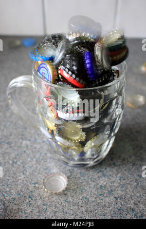 Used beer bottle tops have been collected and are over flowing from a pint jug with a few ghostly ones floating - Stock Photo