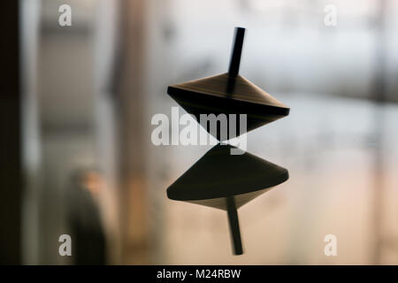 Spinning top in action on a mirror surface - Stock Photo