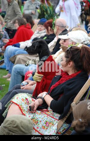 Festival goers sit in deck chairs on the West Hill at the annual Jack In The Green festival at Hastings in East - Stock Photo