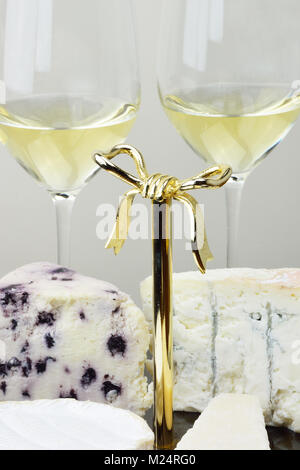 Platter with camembert, parmigiano, gorgonzola and white stilton with blueberries and two glasses white wine - Stock Photo