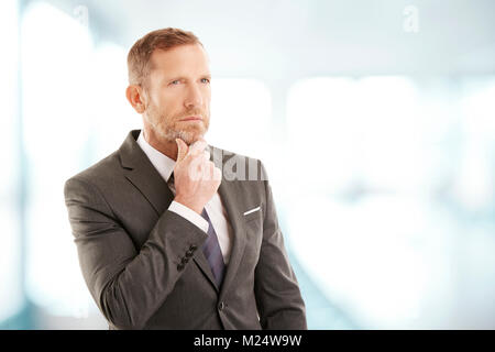 Middle aged businessman wearing suit while standing at the office and seemd deep in thought. Professional man looking - Stock Photo