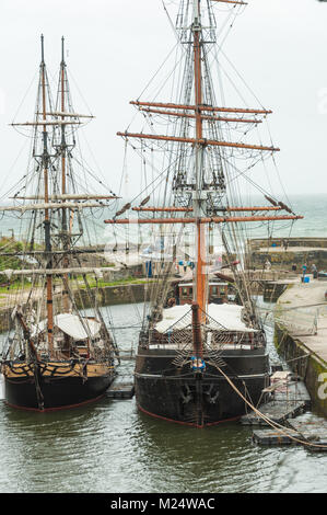 Tall ships Phoenix and Kaskelot moored in the inner harbour at Charlestown, Cornwall, England, UK - Stock Photo