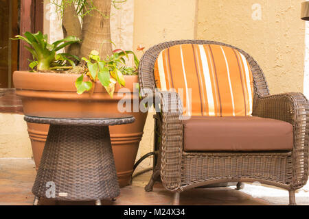 Wicker Chair with Orange striped cushion and terra cotta planter - Stock Photo