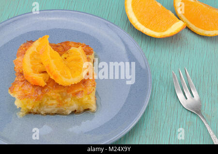 Piece of orange pie in plate with orange twist slice on top and two orange pieces - Stock Photo