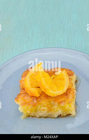 Piece of orange pie in plate with orange twist slice on top - Stock Photo