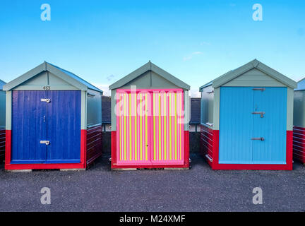 Brighton seafront three beach huts, two with blue doors and the one in the middle has a multi coloured door of yellow, - Stock Photo