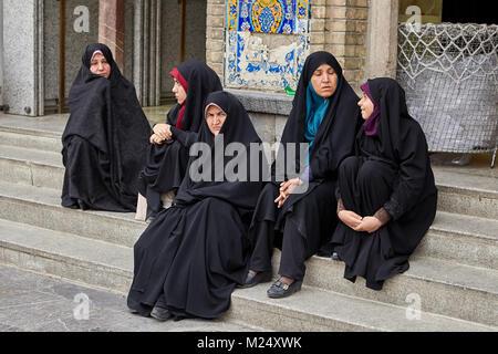 Tehran, Iran - April 27, 2017: Iranian women in hijabs are sitting on the steps near the Shrine of Hazrat Abdulazim - Stock Photo