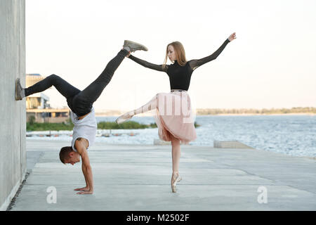 A slender ballerina dances with a modern dancer. Date of lovers. Passion and romance of dance. He stands on his - Stock Photo