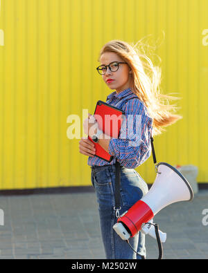 Young attractive girl activist with loudspeaker and tablet pc. She looks at the picture. Call to action - Stock Photo