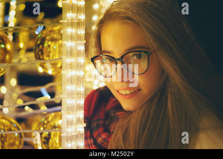 A young sweet hipster girl with glasses and a warm scarf walks by the storefront. She smiles. Portrait at night - Stock Photo