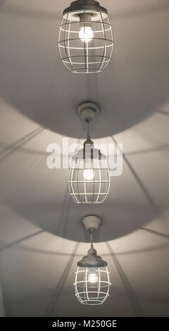 Three lighted and hanging white lamps in white background