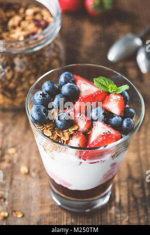 Breakfast yogurt with fresh berries and granola in glass. Selective focus. Healthy lifestyle, clean eating and weight - Stock Photo