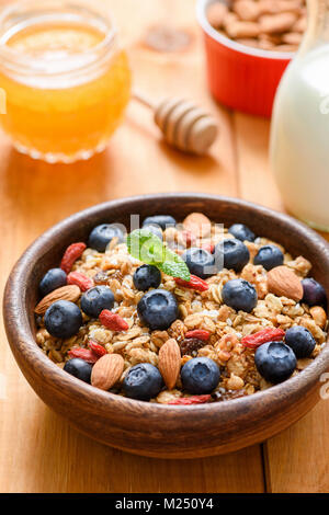 Granola with dried fruits, nuts and fresh blueberries in wooden bowl. Healthy lifestyle, healthy breakfast, dieting - Stock Photo