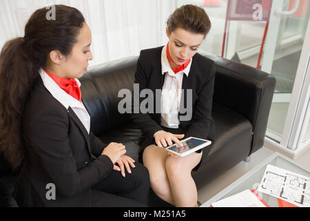 High angle portrait of two real estate agents wearing black and red uniform using digital tablet  sitting on sofa - Stock Photo