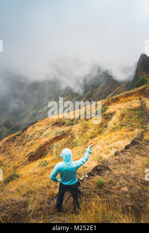 Traveler staying on the cobbled path and admiring clouds flowing over the mountain peaks into the valley. Santo - Stock Photo