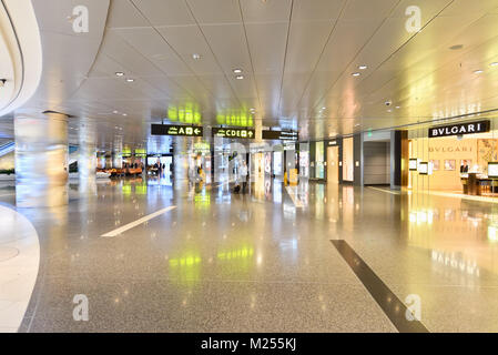 Qatar, Doha, Hamad International Airport. In the transit area, a traveler walks among the premium branded shops - Stock Photo