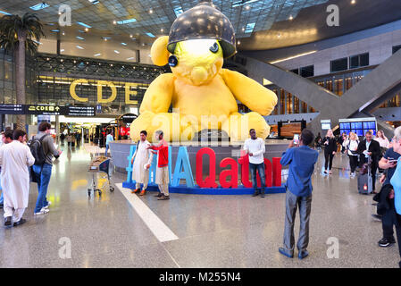 Qatar, Doha, Hamad International Airport. Within the transit area at the main lobby, visitors gather around the - Stock Photo
