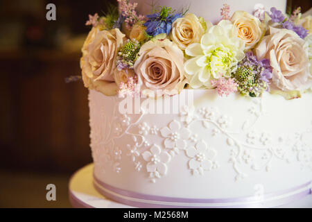Fresh flowers on tier of wedding cake, close up - Stock Photo