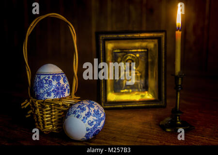 Easter eggs and a burning candle in a candlestick in front of an icon of Jesus Christ on a wooden table against - Stock Photo