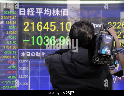 Tokyo, Japan. 6th Feb, 2018. A TV cameraman video tapes a share prices board in Tokyo on Tuesday, February 6, 2018. - Stock Photo
