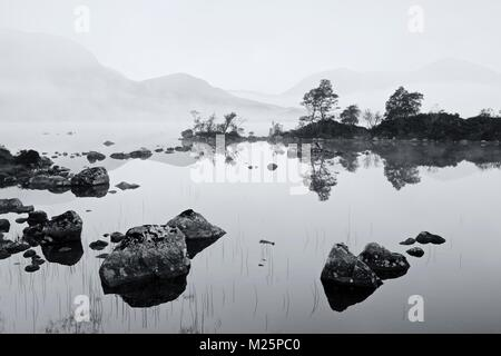 A B&W rendition of a misty sunrise on Rannoch Moor taking from the banks of Lochan na h-Achlaise - Stock Photo