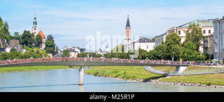 Austria, Salzburg,  People crossing a bridge on the Salzach river with the old town in the background - Stock Photo