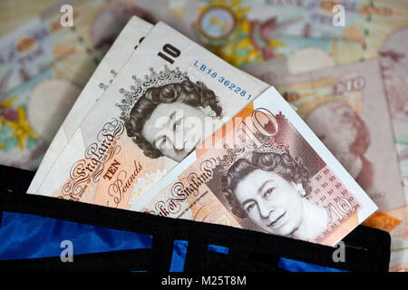 new polymer 10 quid notes with soon to be phased out paper 10 pound notes in a wallet in the uk - Stock Photo