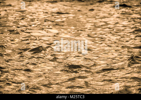 Golden water surface with soft waves abstract background - Stock Photo