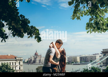 Young happy attractive couple in love is almost kissing and hugging at the background of the magnificent landscape - Stock Photo