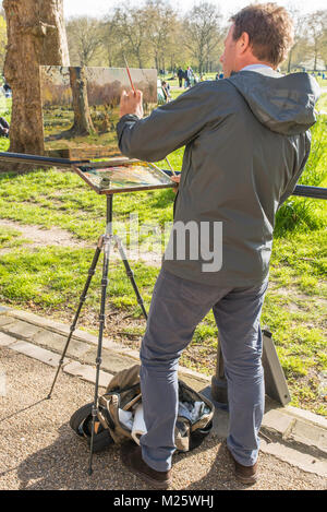 Man painting a picture of people in Green Park in London. He is using an easel and either oil paints or acrylic. - Stock Photo