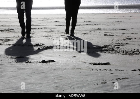 A couple pictured holding hands and walking along the beach in West Wittering, West Sussex, UK. - Stock Photo