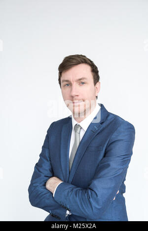 portrait of a smartly dressed middle aged man in a suit looking into camera with his arms folded. Isolated on a - Stock Photo