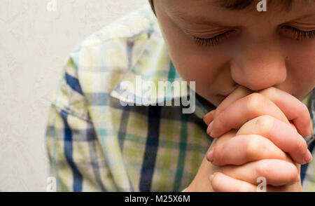 A young boy with his head bowed in prayer - Stock Photo