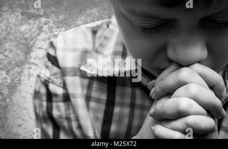 A young boy with his head bowed in prayer. - Stock Photo