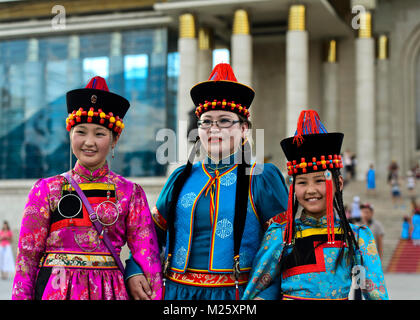 Three young women pose in traditional deel costume and the typical hat with the cone shaped top, Mongolian National - Stock Photo