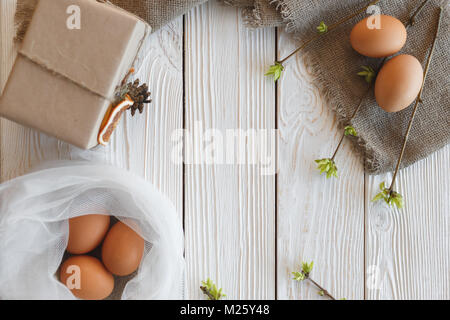 Spring and Easter art. Eggs, branches with green sprouts and a gift box on a white wooden background. - Stock Photo