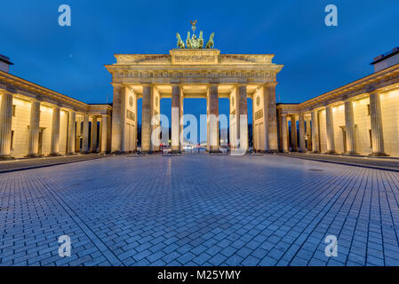 The famous Brandenburg Gate in Berlin illuminated in the early morning - Stock Photo