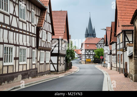 Half-timbered houses at Rimbachstrasse, church tower in distance, in Netra, Ringgau community, Hessen, Germany - Stock Photo